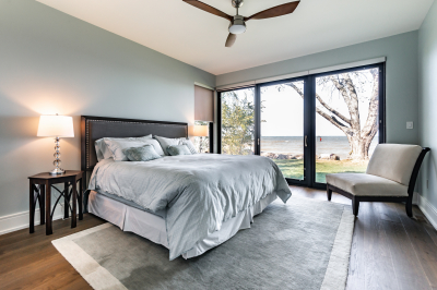 Designs by Santy :: Modern Lakehouse Bedroom with patio door, corner window and lake view