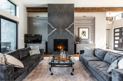 Designs by Santy :: Modern Lakehouse Great room with fireplace, wood beams, large windows and lake view